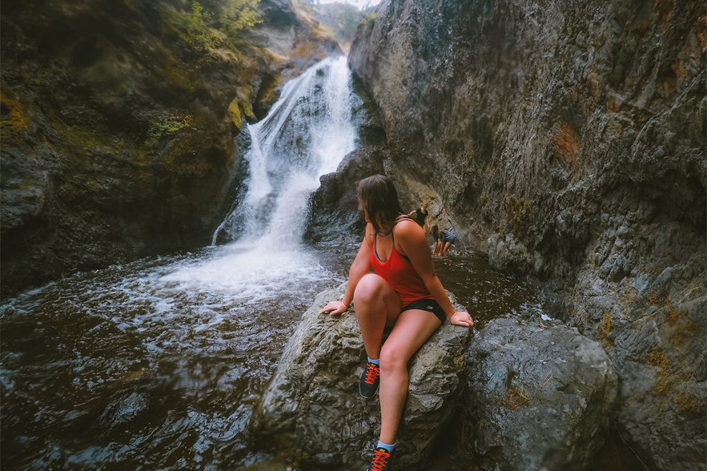 Woman sits on a rock in front of the Bear Creek waterfall