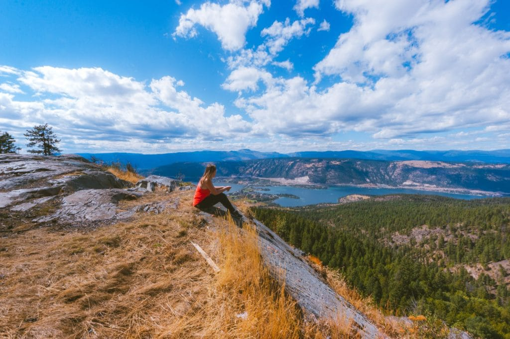 Woman in a red shirt sits on the cliff edge at the Oyama Lookout with views of two lakes in the distance.
