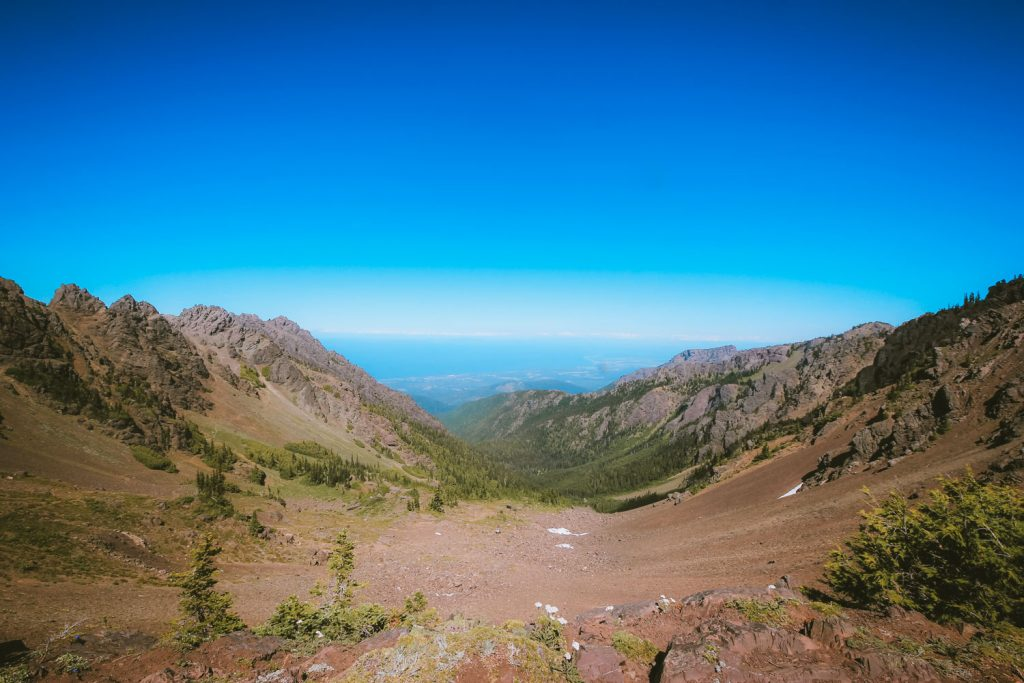 The basin of Klahhane Ridge. Port Angeles and Vancouver Island can be seen distantly in the background.