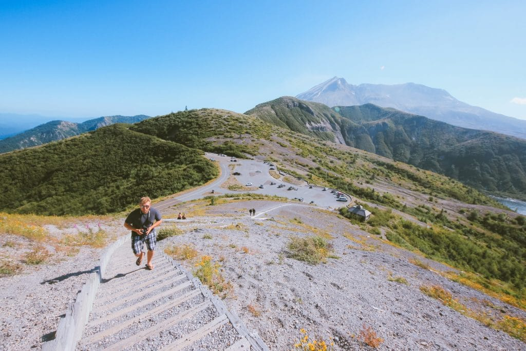 Jacob from Explore the Map climbs the sandladder at Windy Ridge Viewpoint. Mt St Helens towers in the background.