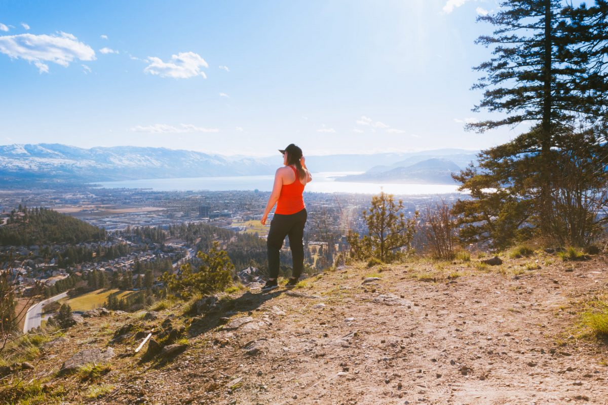 Woman in red looks at Kelowna from the top of Dilworth Water Tower. It's a sunny day.