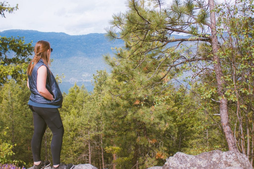 Girl stands in front of Okanagan Lake views from Jack Seaton Park in Lake Country