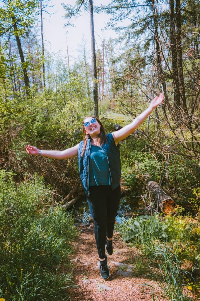 Girl jumping on a forest trail in Lake Country BC