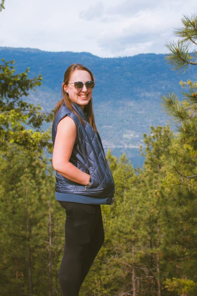 Girl standing in front of an Okanagan Lake view from hiking trails at Jack Seaton Park