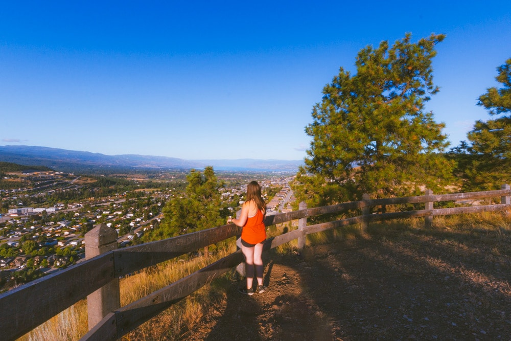 A girl standing near a fence overlooking Kelowna and Black Mountain from the Black Mountain Viewpoint hiking trail