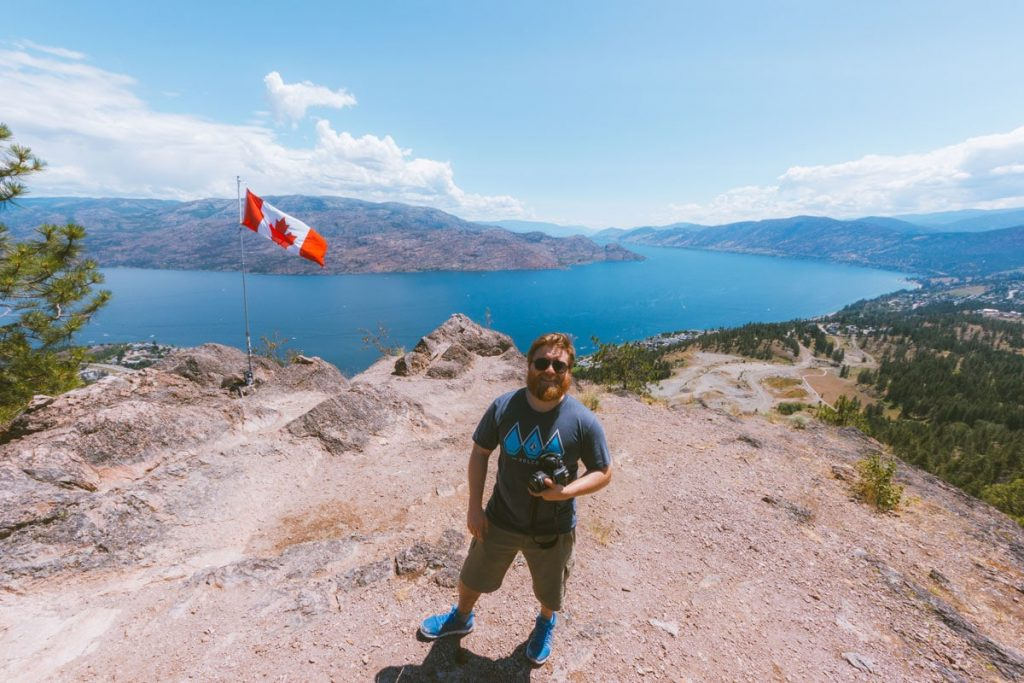 Man stands at the summit of Pincushion Mountain in the central Okanagan