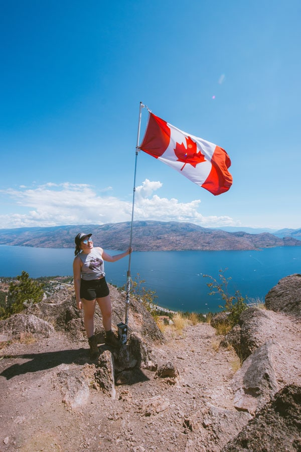 Girl stands with a Canadian flag at the top of Pincushion Mountain