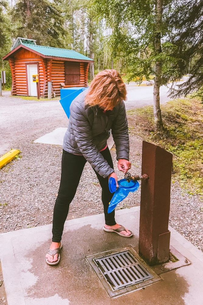 Filling hydration pack with potable water at Liard Hot Springs campground