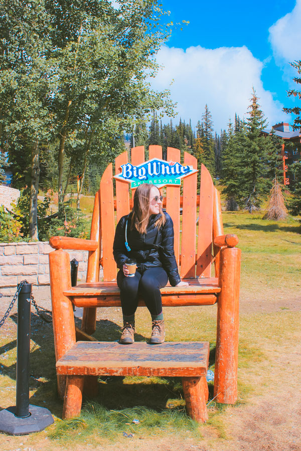 Sam from Explore the Map sits on a large, large chair in the Village at Big White.