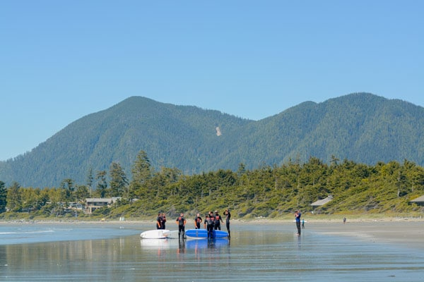 Students learning to surf at Cox Bay beach