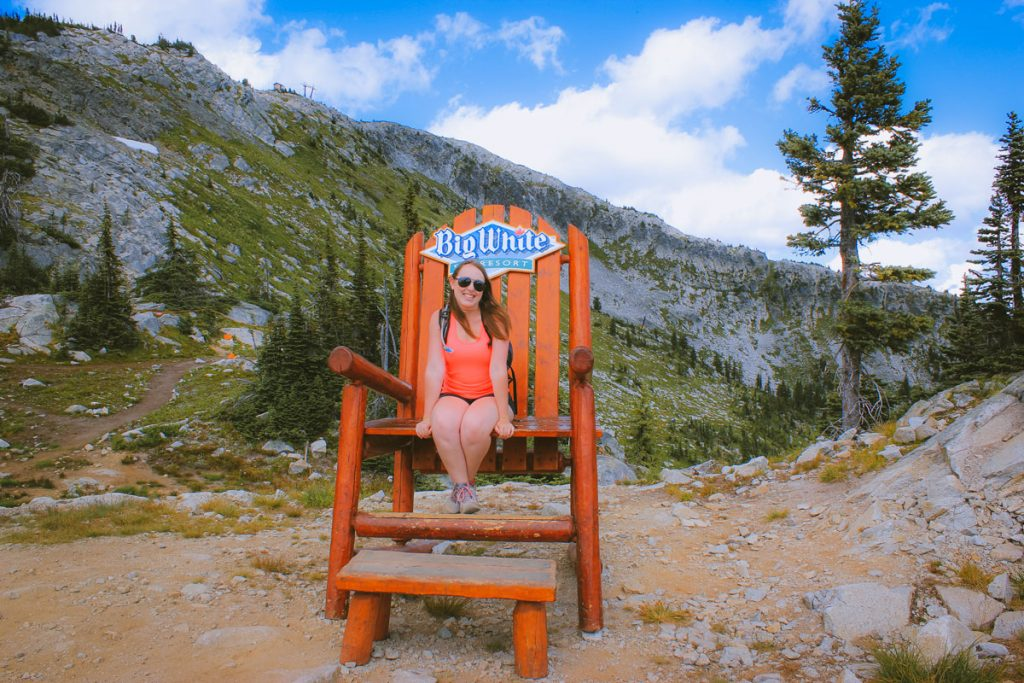 Woman sits on an oversized trail at the trailhead of the Rhonda Lake Trail at Big White Ski Resort