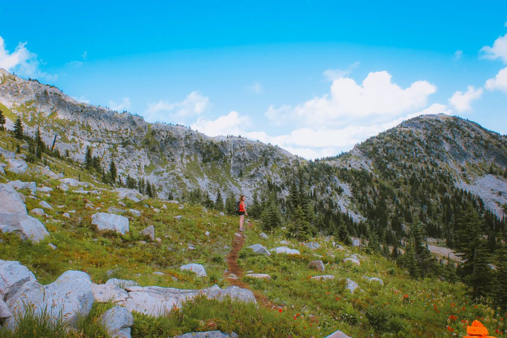 Woman hiking on the rocky Rhonda Lake trail with looming cliffs and alpine forest.