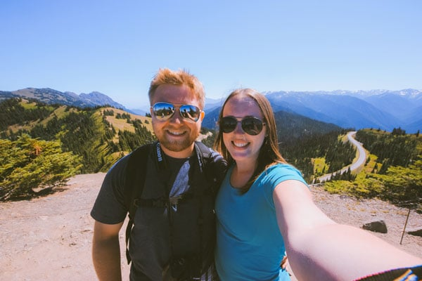 Sam and Jacob from Explore the Map take a selfie while hiking. The Olympic Mountain range disappears in the background.