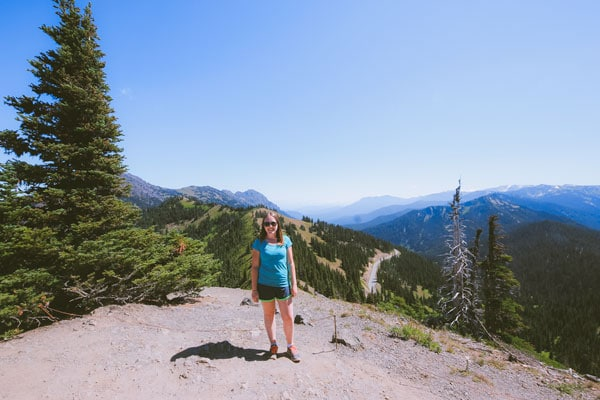Sam from Explore the Map poses for a photo with the Olympic Mountain range.
