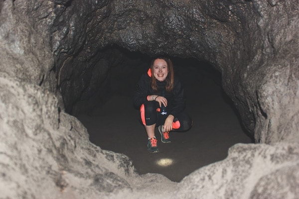 Girl peaks out from the tiny, final chamber of the Lower Caves at Mt St Helens.
