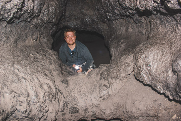 Man looks out from a tiny chamber in the lava tube.