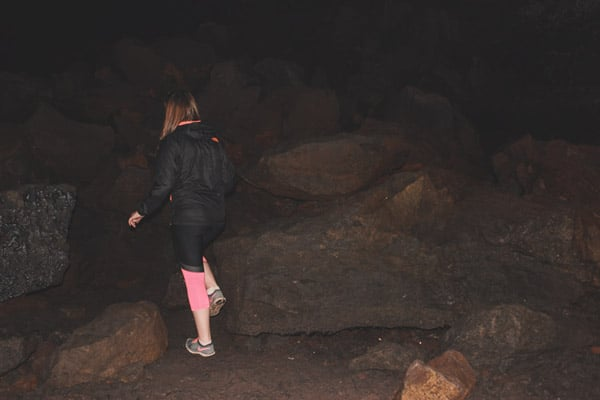Girl climbs over a large boulder pile in a dark lava tube.