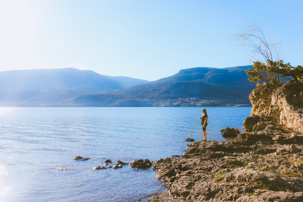 Woman stands on rocks near Okanagan Lake on the Paul's Tomb hike.