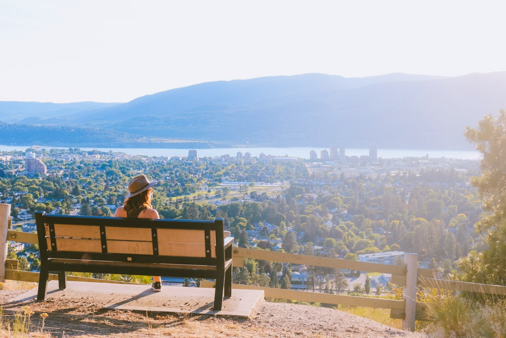 Girl sits on a bench overlooking Kelowna from an easy hiking trail