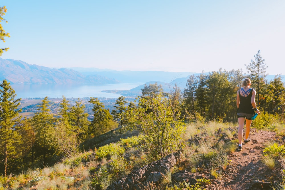 Girl walks along the top of Mt Boucherie with a great view of Okanagan Lake