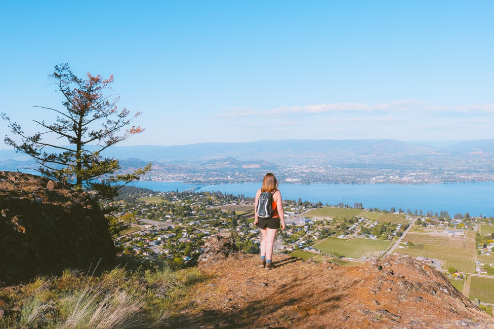 Girl stands at the top of Mt Boucherie with a view Kelowna