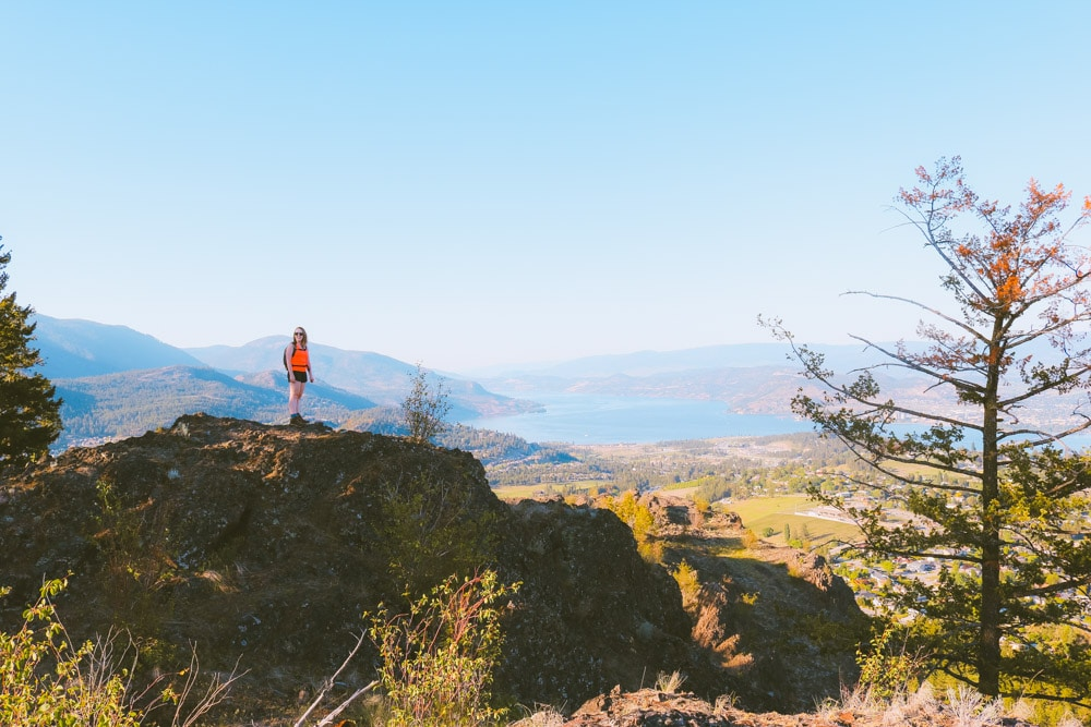 Girl stands on a rock at the summit of the Eain Lamont trail