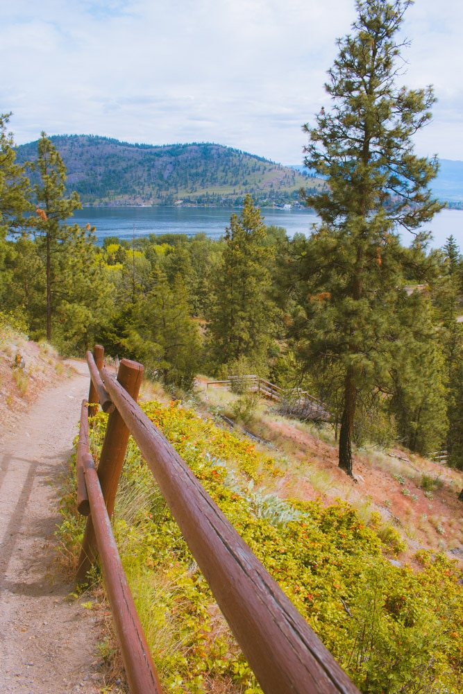 The scenic Canyon Rim trail with wooden handrails with view of Okanagan Lake and Kelowna.