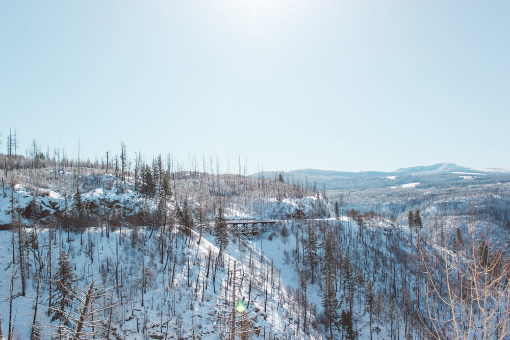 A historic trestles in the distance with a snow covered hill at Myra Canyon