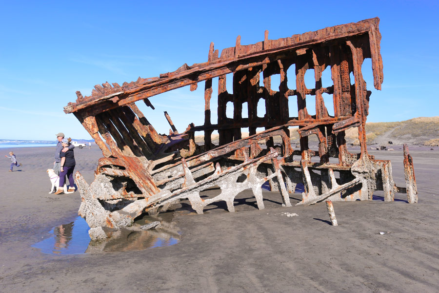 The rusted steel skeleton of the Peter Iredale shipwreck sits in a pool of ocean water.