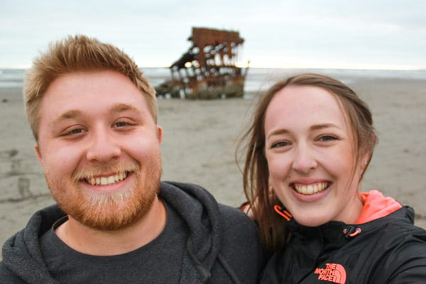 Sam and Jacob from Explore the Map take a selfie with a shipwreck on the Oregon coast.