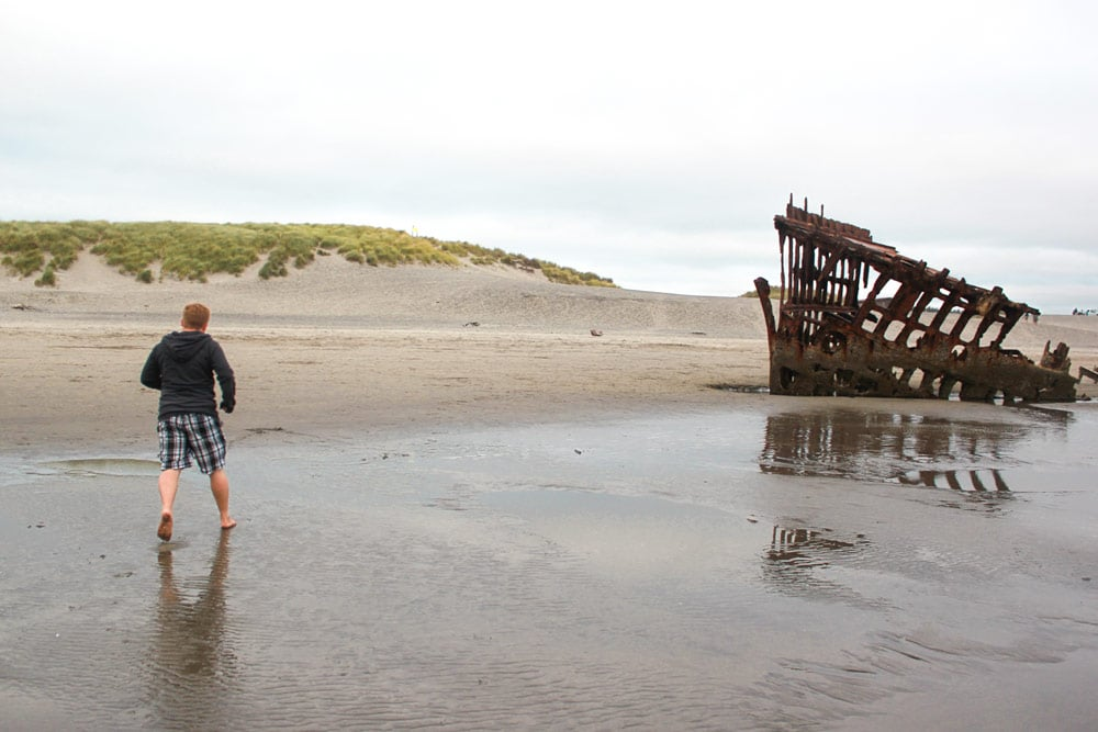 Man runs through the sand towards the Wreck of the Peter Iredale