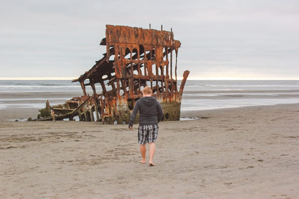 Jacob from Explore the Map walks towards the Peter Iredale shipwreck at Fort Stevens State Park, Oregon.
