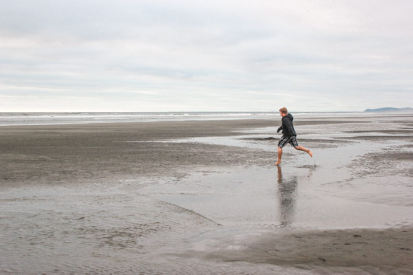 Jacob from Explore the Map jumps among the puddles on Clatsop Beach.
