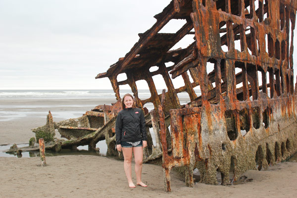 Sam from Explore the Map stands at the base of a shipwreck on the Oregon coast.