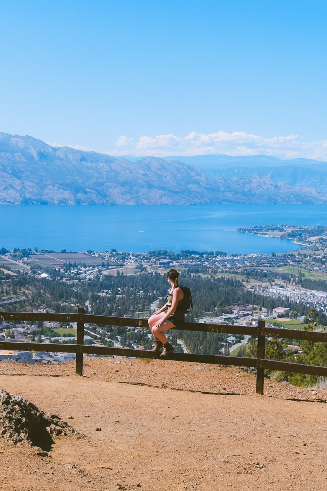 A woman sits on a fence at the summit of the Boucherie Rush Trail in West Kelowna