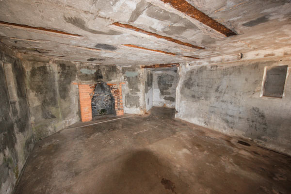 A scary looking room with a brick fireplace.