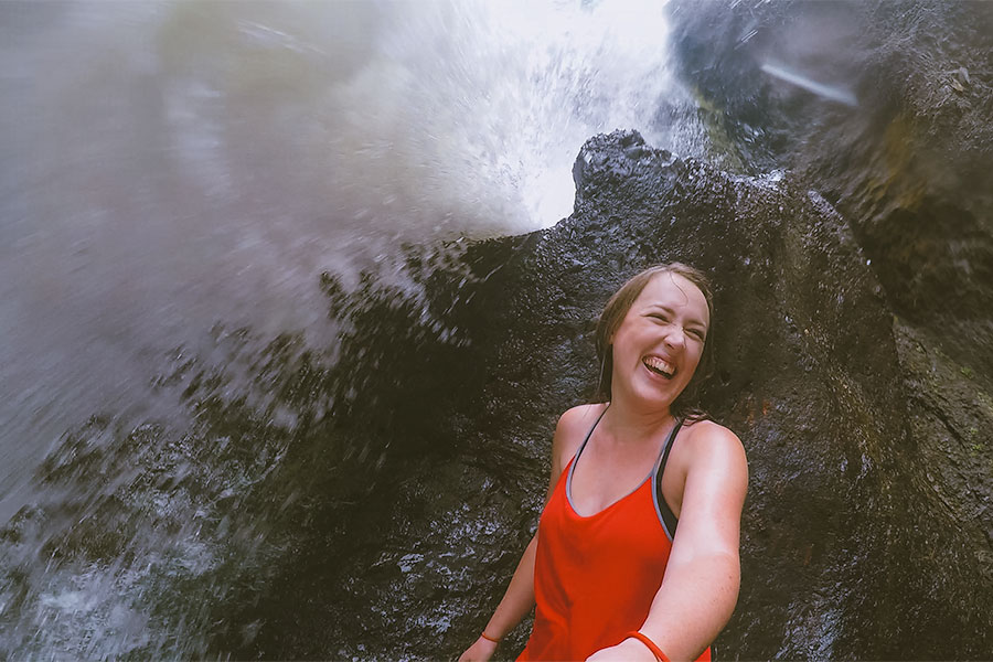 Woman laughs while standing below the Bear Creek waterfall