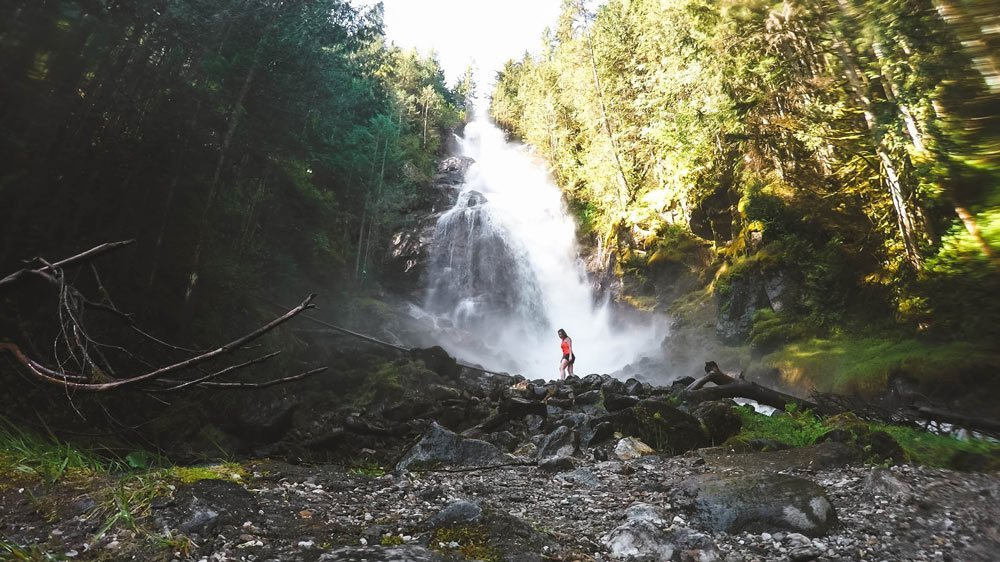 Woman stands near the base of Kay Falls