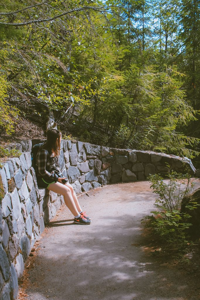 Woman rests on a rock retaining wall