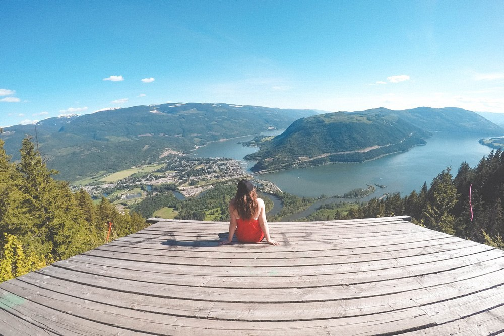 Woman sits on the Sicamous Lookout, overlooking Sicamous and the surrounding valley