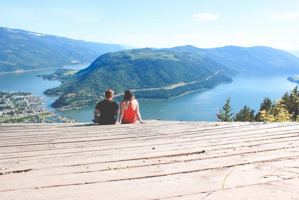 A couple sits on the Sicamous Lookout with spectacular views of the Okanagan Valley