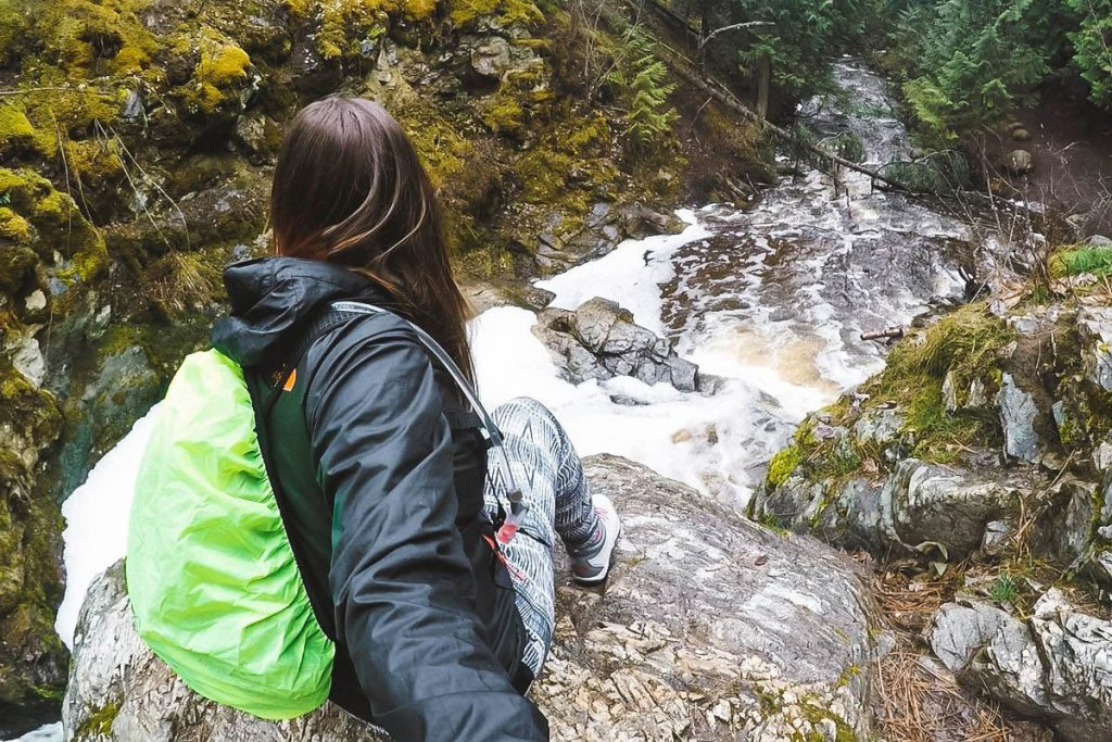 Woman sits at the top of a waterfall at Mill Creek Regional Park