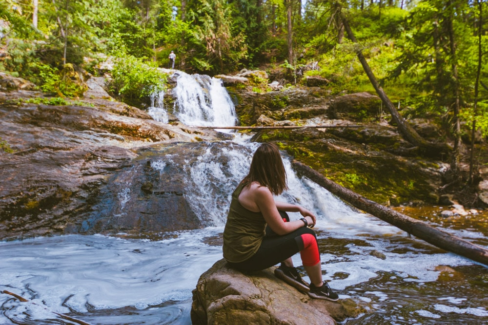 Woman sits on a rock in front of the third waterfall at Mill Creek Regional Park