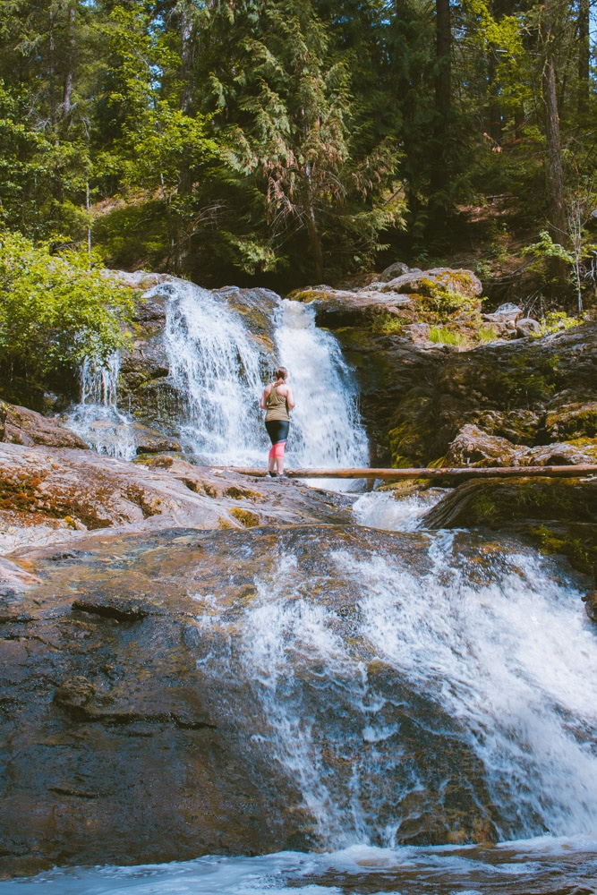 Woman stands in the middle of a waterfall at Mill Creek Regional Park