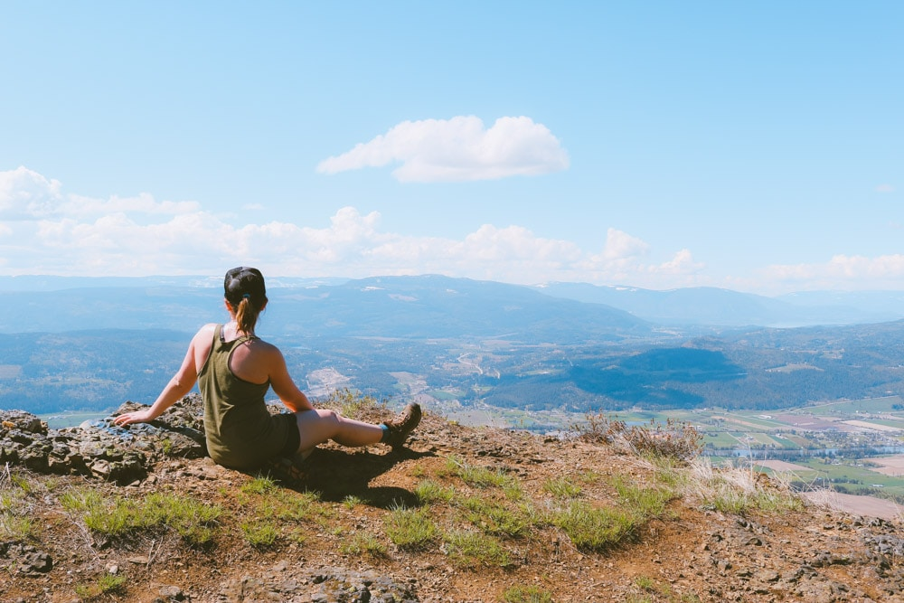 Woman sits near the edge of the summit of the Enderby Cliffs