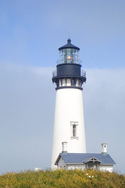 Yaquina Head Lighthouse, Oregon's tallest lighthouse, sits on a hill with a blue sky background.