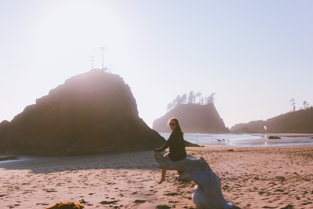 Sam from Explore the map sits on a piece of driftwood at Second Beach in the Pacific Northwest.