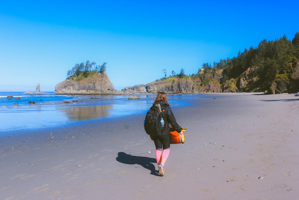 Sam from Explore the Map hikes with camping gear along the sandy shores of Second Beach.