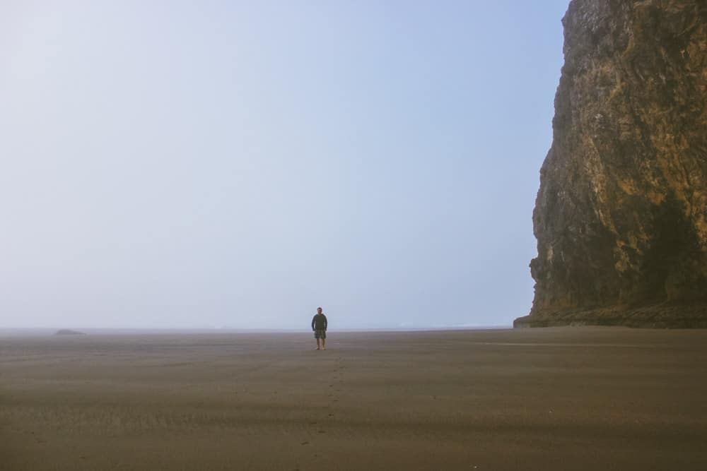 A man stands at the base of the sea stack at Second Beach in the morning mist
