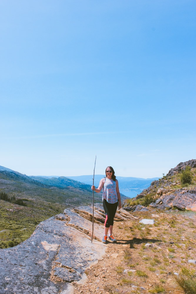 Young woman stands near a cliff edge with a walking stick and view of Okanagan Lake.